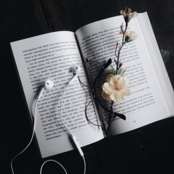 book, glasses, earphones and flowers